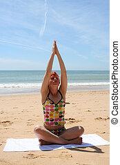 beach yoga 6 - woman does yoga and meditation on beach