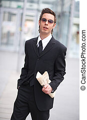 carrying the news - businessman holding a newspaper