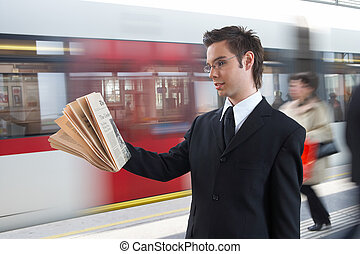 information - businessman reading the newspaper at the train...