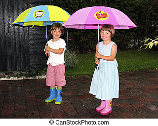 twins with umbrella - twins with colorful umbrellas in the...