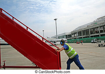 Airport worker pushing a set of stairs for boarding an...