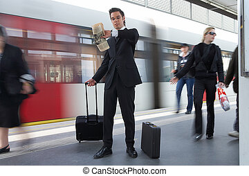 time - businessman at the train station looking at his watch