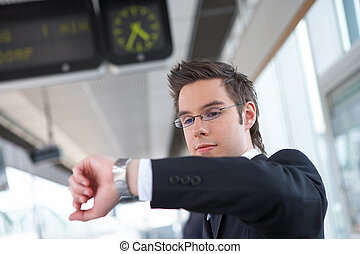 busy - businessman at the train station looking at his watch