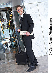 travel - smiling businessman with suitcase an newspaper