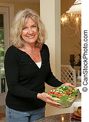 Healthy Salad - A beautiful, mature woman with serving a...