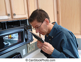 Handy Man Home Repair - Man smelling the old filter that he...