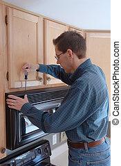 Handy Man Home Repair - Man using a screwdriver to repair...