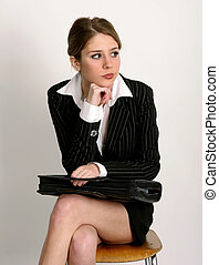 Waiting - Young woman in business suit sitting on chair with...