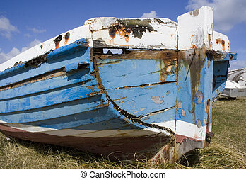 Old blue boat on shore - An un-seaworthy boat beached on the...