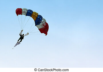 Parachutist Approaching - A skydiver parachuting down from...