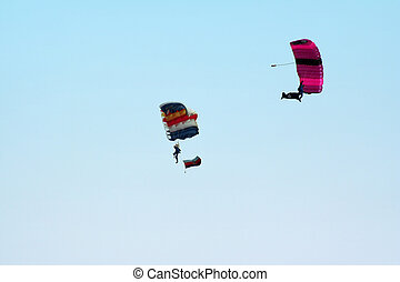 Two Parachutes - Two skydivers suspended from their...