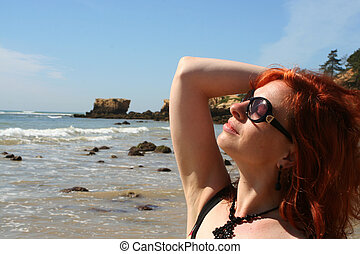 beach babe 3 - woman soaks up the sun at the beach in the...