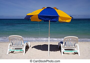 Relaxing in the sun - Two deck chairs with a parasol on a...