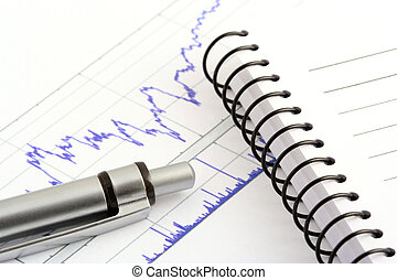pen and notebook on stock chart