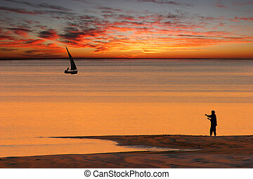 Beach sunset scene in Mozambique with fisherman and small...