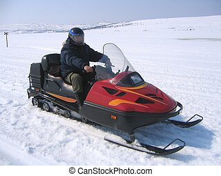 Snowmobile riding - Man riding a red snowmobile