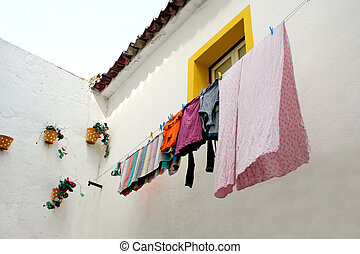 hanging laundry - wall with decorative pots and laudry...