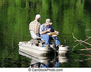 Men Fishing in Boat - Two men fishing in a boat on a lake