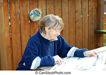 Senior woman reading newspaper on a deck