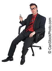 cool - businessman sits in chair holding a mobile phone and...
