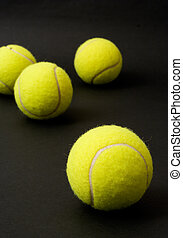 Tennis balls - Yellow tennis balls isolated on a black...