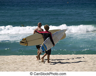 surfers - photo of father and son surfers, taken on beach at...