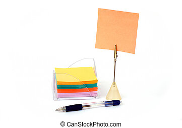 Blank note on stand with stack of notes in holder and pen...