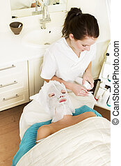 Facial Mask Detail - Lotion being applied to the face during...