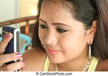 talking on phone - filipina reading a text message