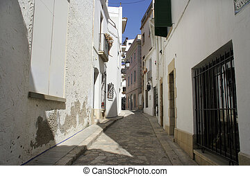 sitges street - narrow cobbled street in the catalonian town...