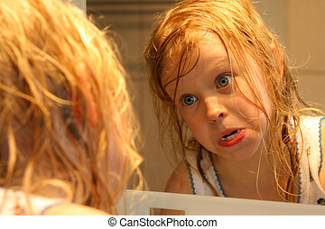 In front of a mirror - Little girl making faces in front of...