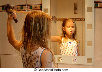 In front of a mirror - Little girl brushing her hair in...