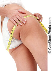 Cellulite - Woman with measuring tape looking for cellulite
