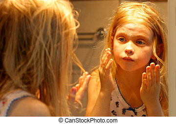 In front of a mirror - Little girl creaming her face in...