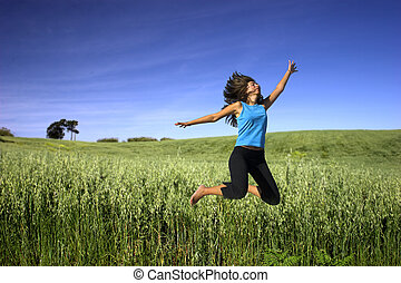 Jumping -  Young active woman jumping on a green field
