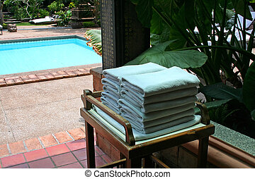 Poolside towels - Towels next to the pool in a tropical...