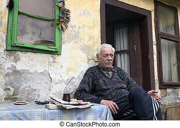 old man sitting and smoking