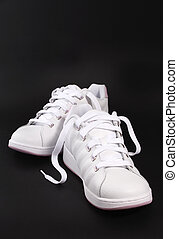 a pair of shoes against black background
