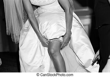 Bride and garter at we - Bride slipping garter on leg at...