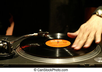 Scratching a record - A DJ scratches the record, hand...