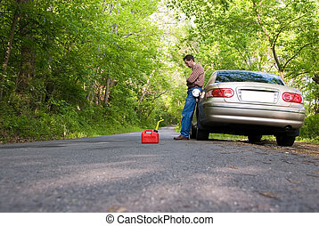 Out Of Gas - Upset man stranded on a country road, with a...