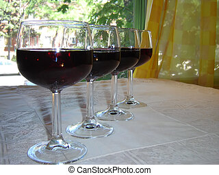 Four glasses of wine in front a window in front a window