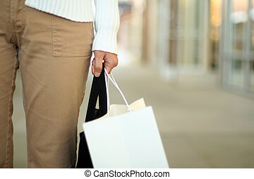 Shopping - A woman shopping, carrying a bag