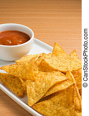 Tortilla chips and a cup of mexican chilli sauce