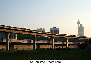 Elevated train tracks, city skyline in the early morning