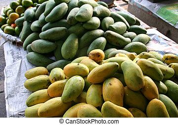 Mangoes - Ripe and green mangoes in piles in the marketplace