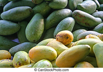 Mangoes - Ripe and green mangoes in piles