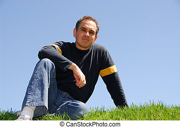 Man sitting on grass, cloudless sky background
