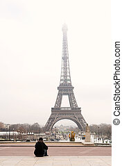 Paris #42 - A person sitting, looking at the Eiffel Tower in...