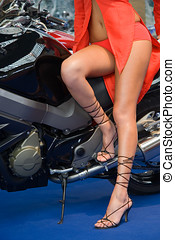 Woman Legs - Legs of a woman standing on a motorbike.